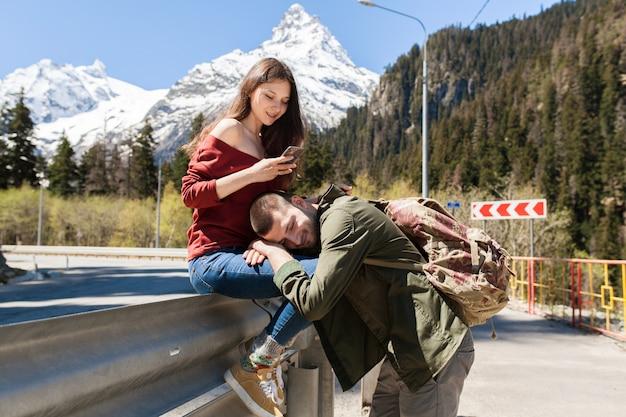 流行に敏感な若いカップルの愛、道路に座って