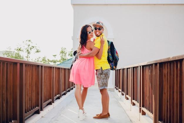 Молодая хипстерская красивая пара в любви, стильный летний наряд, путешествие с рюкзаком, отпуск, солнцезащитные очки, красочные, улыбающиеся, счастливые, позитивные, романтические, объятия