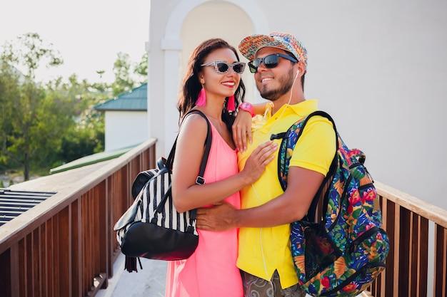 恋に若いヒップスターの美しいカップル、スタイリッシュな夏の服装、バックパック、休暇、サングラス、カラフル、笑顔、幸せ、前向き、ロマンチック、抱擁と一緒に旅行