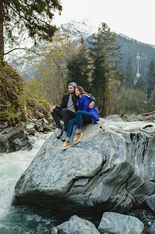 Молодой битник красивая влюбленная пара гуляет по скалам у реки в зимнем лесу