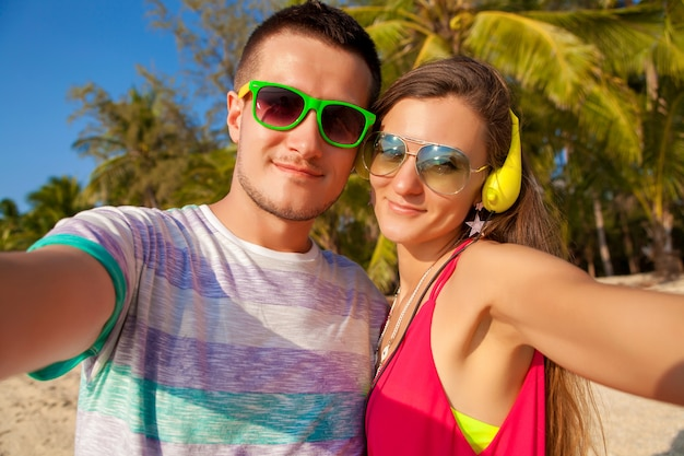 Young hipster beautiful couple in love making selfie photo on tropical beach, summer vacation, happy together, honeymoon, colorful style, sunglasses, headphones, smiling, happy, having fun, positive