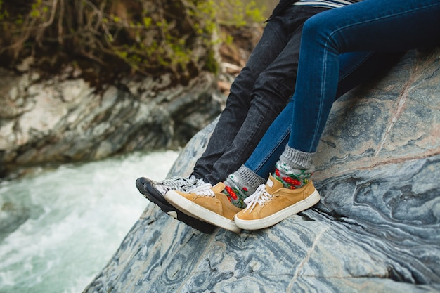 Young hipster beautiful couple in love sitting on a rock at river in winter forest