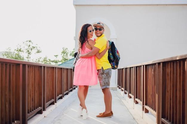 Coppia giovane hipster bella innamorata, vestito estivo elegante, in viaggio con zaino, vacanze, occhiali da sole, colorato, sorridente, felice, positivo, romantico, abbracciando