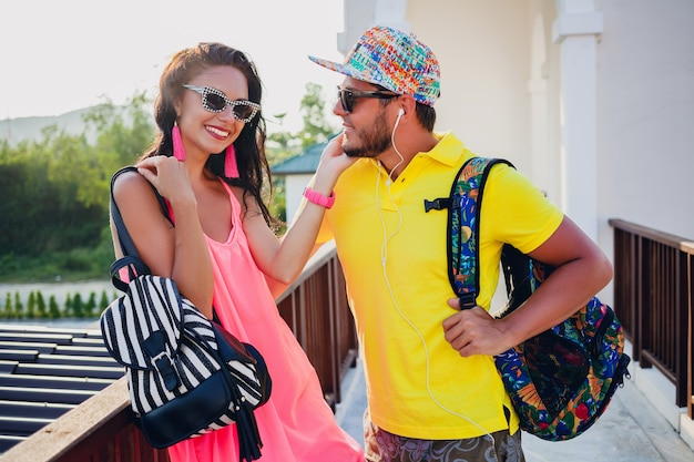 Young hipster beautiful couple in love, stylish summer outfit, traveling with backpack, vacation, sunglasses, colorful, smiling, happy, positive, romantic, hugging