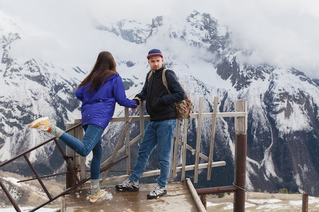 Young hipster beautiful couple in love, walking in mountains