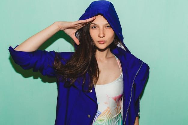 Молодая хипстерская красивая женщина, синяя позирует на синей стене, модный летний тренд купальника, крутое выражение лица