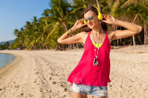 Young hipster beautiful woman, tropical beach, vacation, colorful, summer trend style, sunglasses, headphones, listening to music, palm trees background, smiling happy, fun, details, close up portrait