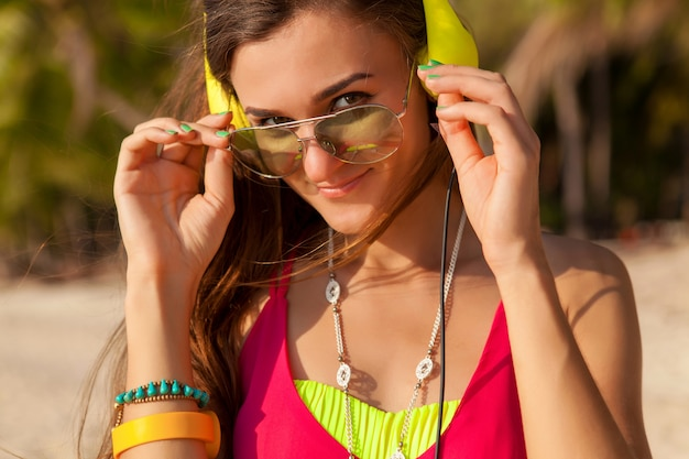 Giovane hipster bella donna, spiaggia tropicale, vacanza, colorato, stile di tendenza estiva, occhiali da sole, cuffie, ascolto di musica, sfondo di palme, sorridente felice, divertimento, dettagli, ritratto