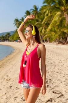 Молодая хипстерская красивая женщина, тропический пляж, отпуск, красочный, летний трендовый стиль, солнцезащитные очки, наушники, слушать музыку, фон пальм, счастливый улыбающийся, веселье, детали, портрет крупным планом