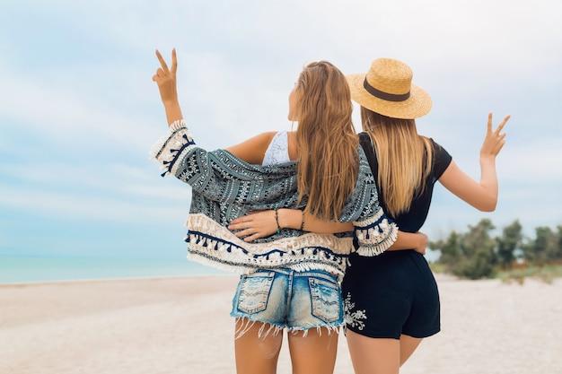Молодые хипстерские красивые женщины на отдыхе на тропическом пляже, стильный летний наряд, счастливая, модная тенденция, стиль хиппи, модные аксессуары, подруги вместе, позитивное настроение, вид со спины