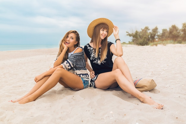 Young hipster beautiful women on vacation on tropical beach sitting on sand, stylish summer outfit, smiling happy, fashion trend, boho style, sexy legs, girls friends having fun together