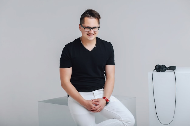 Young hipster in a black t-shirt, white trousers and glasses are sitting on a tuba.