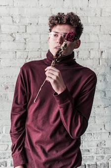 Un giovane hipster che posa con una rosa secca e indossa un dolcevita rosso