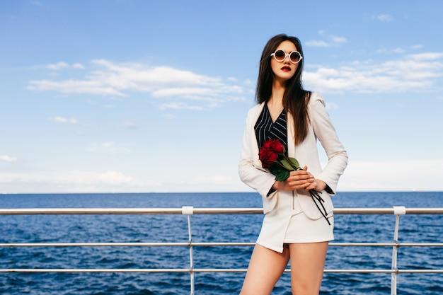 バラの小さな赤い花束と堤防でポーズをとって若い流行に敏感なブルネットの女性