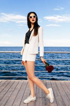 Donna castana giovane hipster in posa all'argine con piccolo mazzo di rose rosso