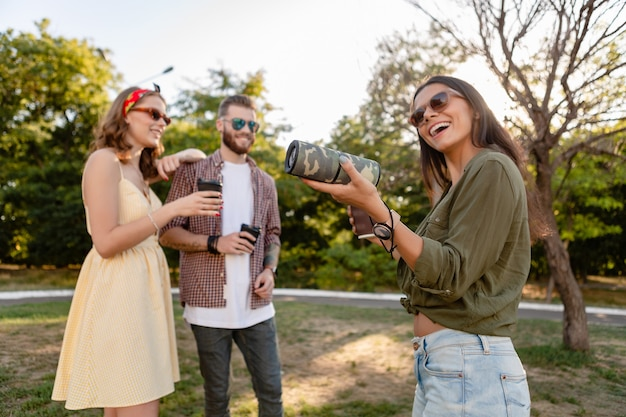 Compagnia di giovani hipster di amici che si divertono insieme nel parco sorridendo ascoltando musica su altoparlante wireless, stagione estiva