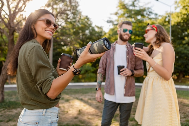 Young hipster company of friends having fun together in park smiling listening to music on wireless speaker