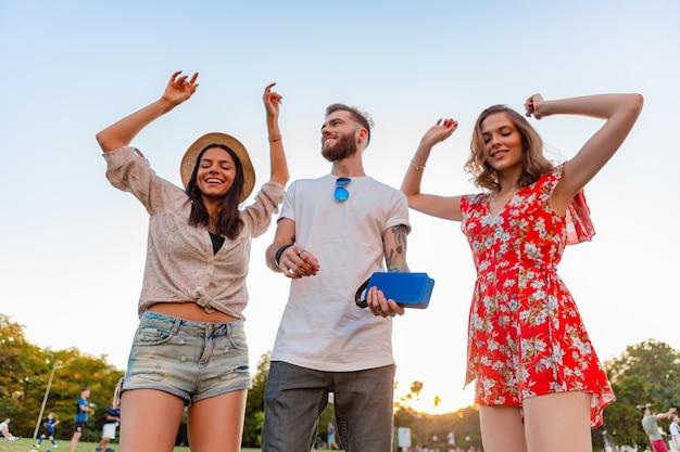 Giovane compagnia hipster di amici che si divertono insieme nel parco sorridendo ascoltando musica su altoparlanti wireless