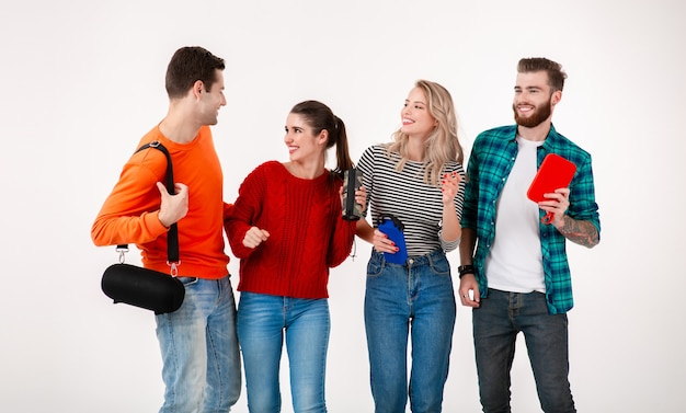 Young hipster company of friends having fun together smiling listening to music on wireless speakers, dancing laughing isolated studio white background in colorful stylish outfit