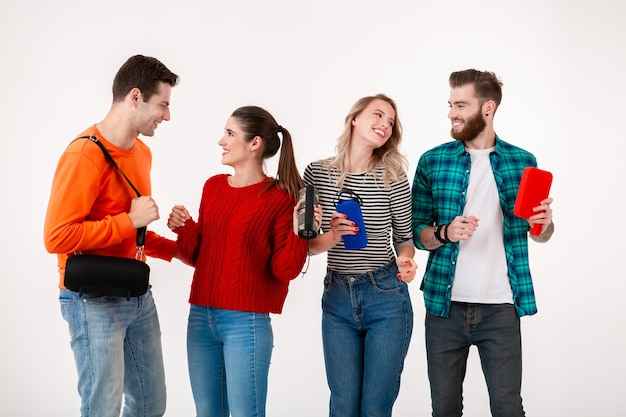 Young hipster company of friends having fun together smiling listening to music on wireless speakers, dancing laughing