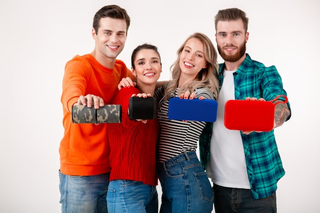 Young hipster company of friends having fun together smiling listening to music on wireless speakers, isolated  white wall in colorful stylish outfit, showing devices in camera