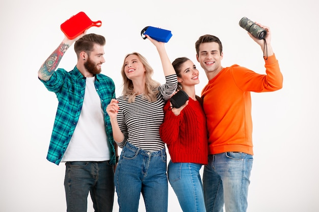 Young hipster company of friends having fun together smiling listening to music on wireless speakers
