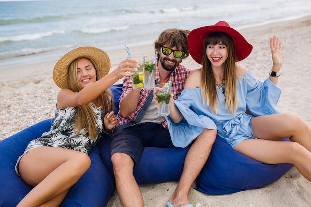 Giovane compagnia hipster di amici in vacanza al bar sulla spiaggia, bevendo cocktail mojito, felice positivo, stile estivo, sorridendo felice, due donne e un uomo che si divertono insieme, parlando, flirtare, romanticismo, tre