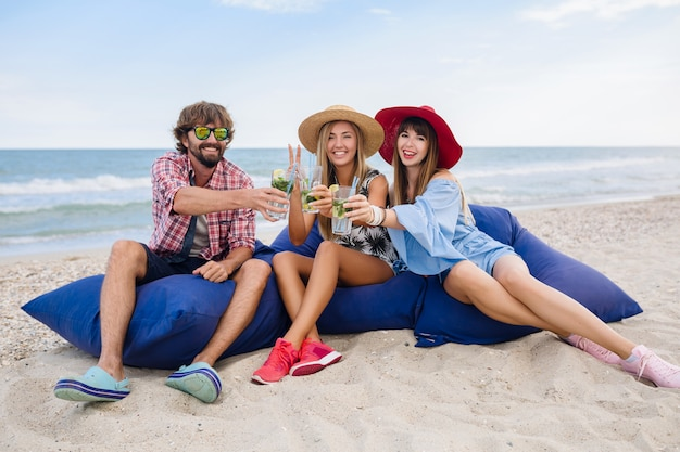 Young hipster company of friends on vacation at beach cafe, drinking mojito cocktail