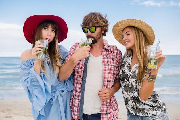 Giovane compagnia hipster di amici in vacanza in spiaggia, bevendo cocktail mojito, felice positivo, stile estivo, sorridendo felice, due donne e un uomo che si divertono insieme, parlando, flirt, romanticismo, tre