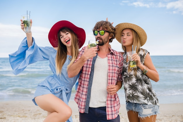Young hipster company of friends on vacation at beach, drinking mojito cocktail