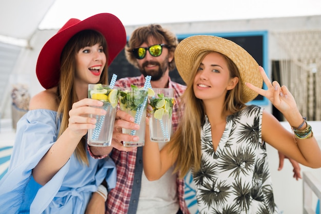 Young hipster company of friends on vacation at summer cafe, drinking mojito cocktails, happy positive style, smiling happy, two women and man having fun together, talking, flirt, romance, three
