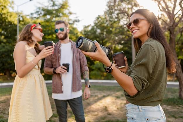 Молодая хипстерская компания друзей веселится вместе в парке, улыбаясь, слушая музыку на беспроводной динамик, летний сезон
