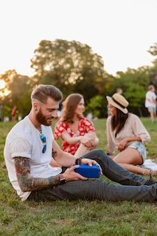 무선 스피커로 음악을 들으며 웃고 있는 공원에서 함께 즐거운 시간을 보내는 친구들의 젊은 힙스터 회사