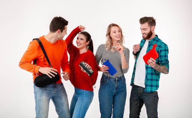 Молодая хипстерская компания друзей веселится вместе, улыбаясь, слушая музыку на беспроводных колонках