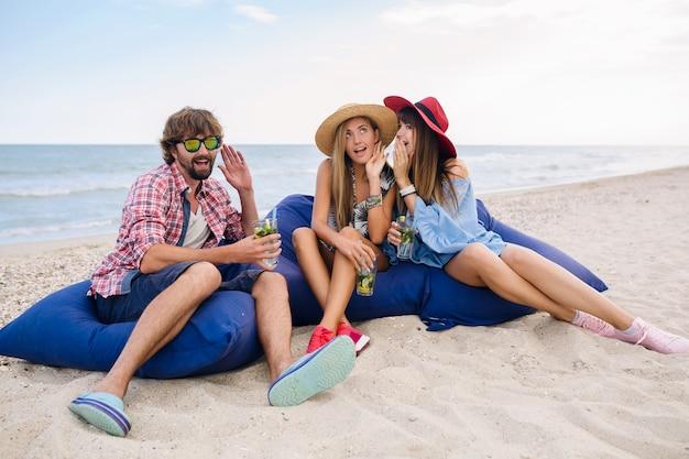 Молодая хипстерская компания друзей на отдыхе в пляжном кафе, пить коктейль мохито, счастливый позитив, летний стиль, счастливые улыбки, две женщины и мужчина веселятся вместе, разговаривают, флирт, романтика, три