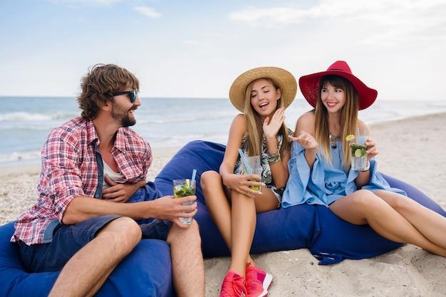 ビーチカフェでの休暇に友人の若いヒップな会社、モヒートカクテルを飲んで、幸せな肯定的な夏のスタイル、幸せな笑顔、2人の女性と男性が一緒に楽しんで、話して、浮気、ロマンス、3