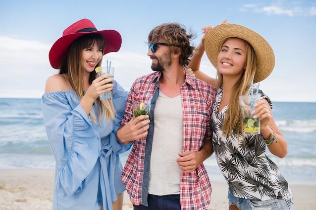 Молодая хипстерская компания друзей на отдыхе на пляже, пьющая коктейль мохито, счастливый позитив, летний стиль, счастливая улыбка, две женщины и мужчина веселятся вместе, разговаривают, флирт, романтика, три