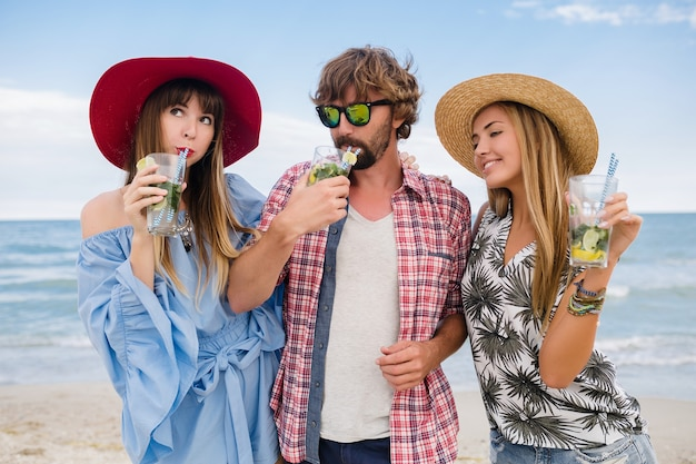 ビーチでの休暇で友達の若いヒップな会社、モヒートカクテルを飲んで、幸せな肯定的な夏のスタイル、幸せな笑顔、2人の女性と男性が一緒に楽しんで、話して、浮気、ロマンス、3