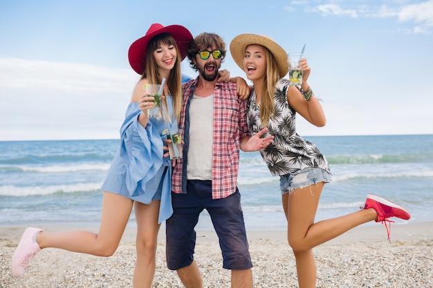 モヒートカクテルを飲み、ビーチでの休暇に友達の若い流行に敏感な会社