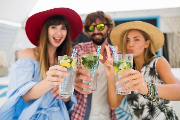 夏のカフェで休暇中に友人の若いヒップな会社、モヒートカクテルを飲んで、幸せな肯定的なスタイル、幸せな笑顔、2人の女性と男性が一緒に楽しんで、話して、浮気、ロマンス、3