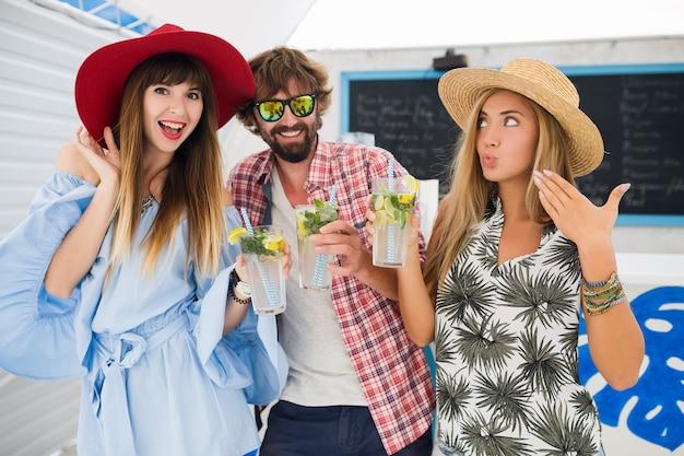 Молодая хипстерская компания друзей на отдыхе в летнем кафе, пьет коктейли мохито, счастливый позитивный стиль, счастливые улыбки, две женщины и мужчина веселятся вместе, разговаривают, флирт, романтика, три