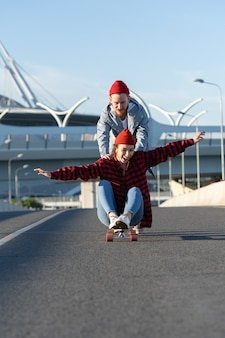 Young hipster couple have fun on longboard outdoors riding city road cheerful laughing together