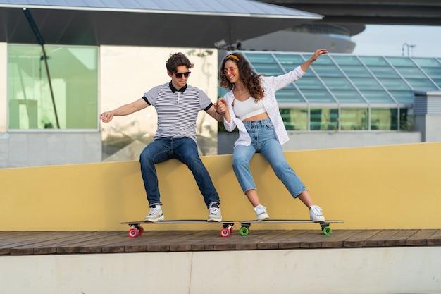 젊은 힙스터 커플은 도시 스케이트파크에 앉아 있는 롱보드 척 타는 스케이트보드로 즐거운 시간을 보낸다