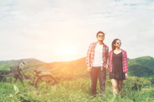 Young hipster couple holding hands walking on the meadow relaxin