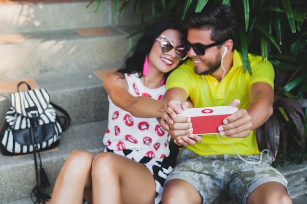 Молодая хипстерская влюбленная пара, слушающая музыку на динамике, счастливая улыбка, веселье, летний наряд, тропический отдых, солнцезащитные очки