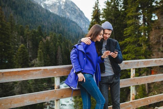 山の冬の休暇に愛の流行に敏感な若いカップル