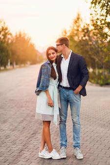 Молодая пара битник в любви открытый. сногсшибательный чувственный портрет молодой стильной пары моды представляя в заходе солнца лета. хорошенькая молодая девушка в джинсовой куртке и ее красивый парень пешком.