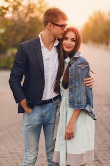 屋外の愛の流行に敏感な若いカップル。夏の日没でポーズをとってスタイリッシュなファッションの若いカップルの見事な官能的な肖像画。ジーンズのジャケットと歩いている彼女のハンサムなボーイフレンドのかなり若い女の子。