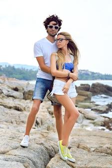 夏の時間に一緒に愛の流行に敏感な若いカップル。驚くほど美しい石のビーチでポーズをとり、スタイリッシュなカジュアルな服を着て、抱擁し、楽しんでいます。