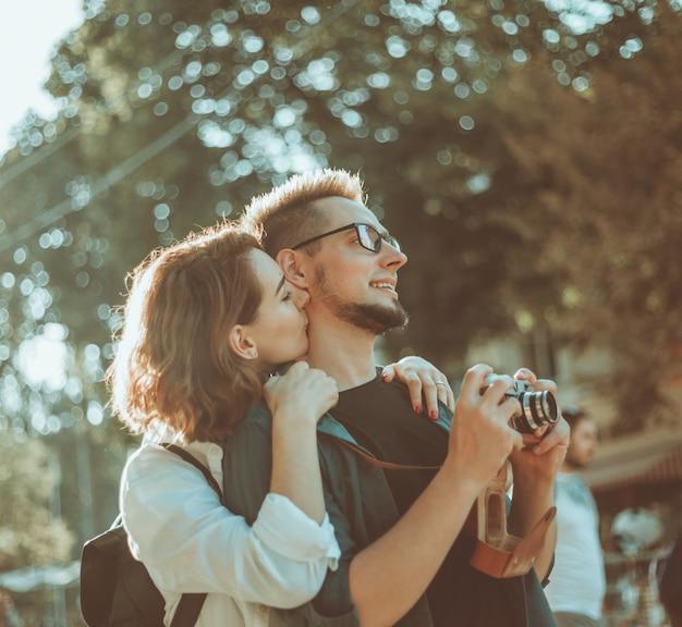 레트로 카메라로 도시의 거리를 따라 산책하는 사랑 관광에 젊은 힙 스터 커플
